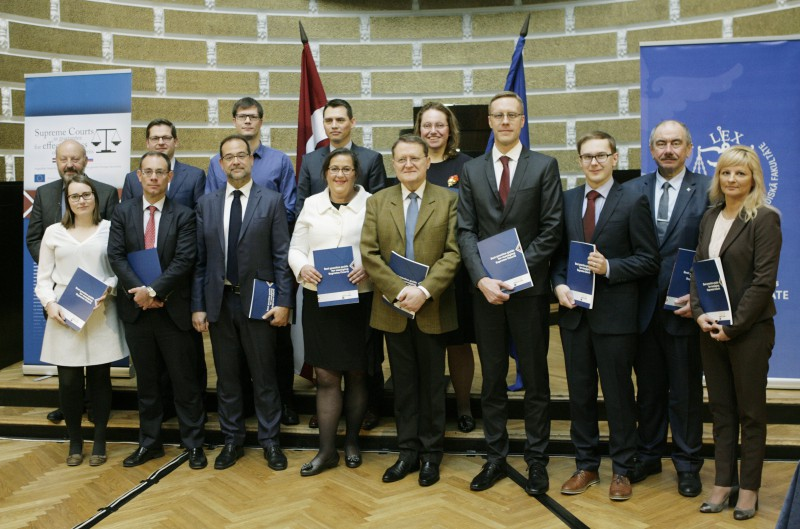 Project participants from the Supreme Courts of Latvia, Lithuania, Hungary and Spain, and Universities of Antwerp and Ljubljana holding the result of successful cooperation – Handbook